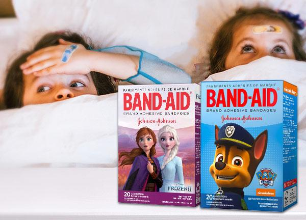 Two Band-Aid boxes for kids against a background of two kids in bed